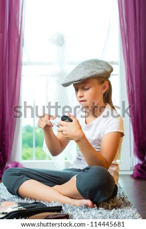 Family - child or teenager sitting with cap in room on the floor and is doing make-up - stock photo