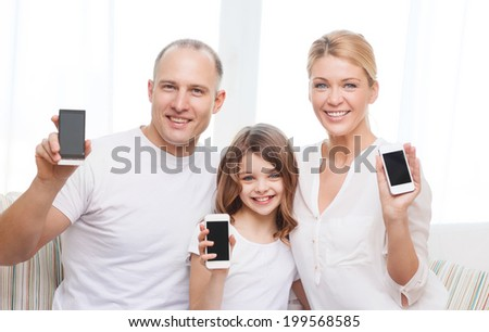 family, child, technology and home concept - smiling parents and little girl with blank black screen smartphones at home - stock photo