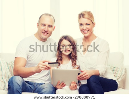 family, child, technology, money and home concept - smiling parents and little girl with tablet pc and credit card at home