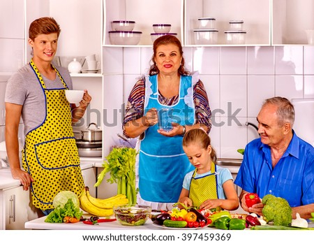 Family child with father cooking at kitchen. Grandfather and grandmother. - stock photo