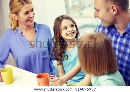 family, childhood, breakfast and people - happy parents and children drinking tea with cups at home - stock photo