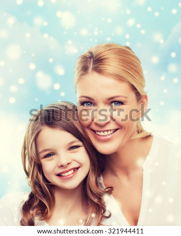 family, childhood, happiness and people - smiling mother and little girl over blue sky and snow background