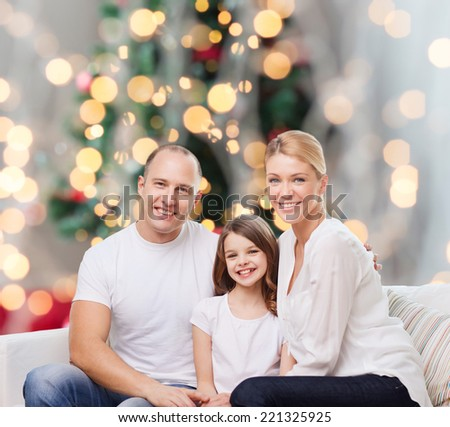 family, childhood, holidays and people - smiling mother, father and little girl over christmas tree lights background - stock photo