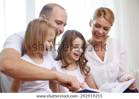 family, childhood, holidays and people - smiling mother, father and little girls reading book at home - stock photo