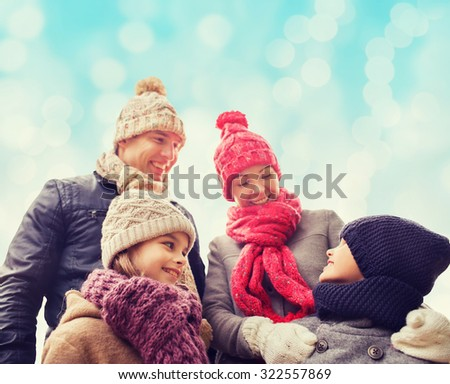 family, childhood, season and people concept - happy family in winter clothes over blue lights background - stock photo