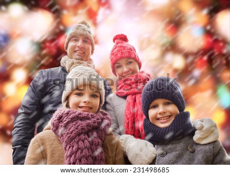family, childhood, season, holidays and people concept - happy family in winter clothes over red lights and snow background - stock photo