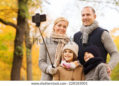 family, childhood, season, technology and people concept - happy family photographing with smartphone and selfie stick in autumn park - stock photo