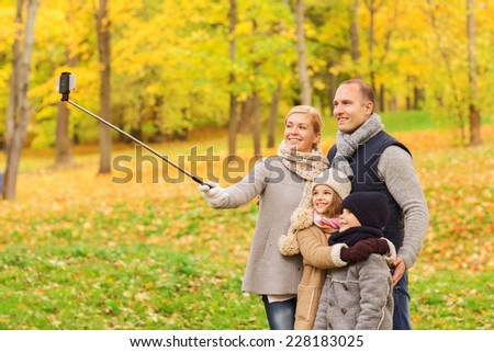 family, childhood, season, technology and people concept - happy family taking selfie with smartphone and monopod in autumn park - stock photo