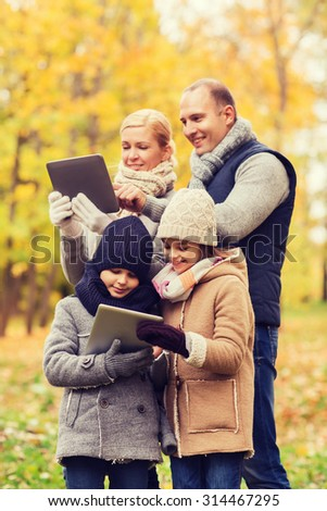 family, childhood, season, technology and people concept - happy family with tablet pc computers in autumn park - stock photo