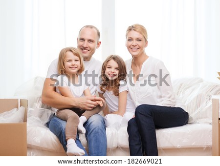 family, children, accomodation and home concept - smiling parents and two little girls moving into new home - stock photo