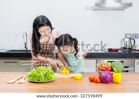 family, children and happy people concept - Asian mother and kid daughter cooking in the kitchen at home. Looking happy family - stock photo