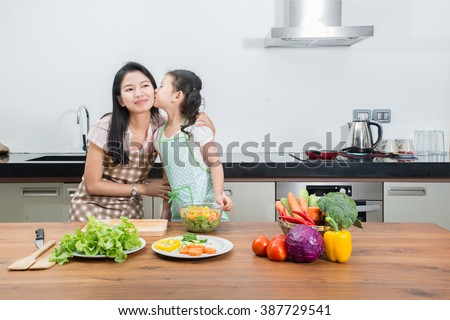 family, children and happy people concept - Asian mother and kid daughter cooking in the kitchen at home. Asian mother and kid looking happy family.  - stock photo