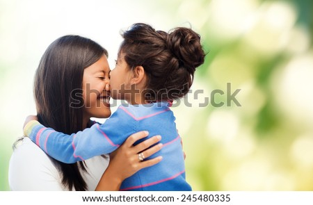 family, children and happy people concept - happy little girl hugging and kissing her mother over green background - stock photo