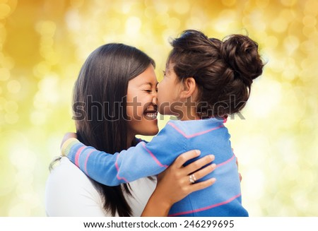 family, children and happy people concept - happy little girl hugging and kissing her mother over yellow lights background - stock photo