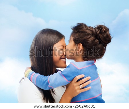family, children and happy people concept - happy little girl hugging and kissing her mother over blue sky background - stock photo
