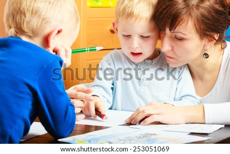 Family, children and happy people concept. Mother and sons drawing together, mom helping with homework