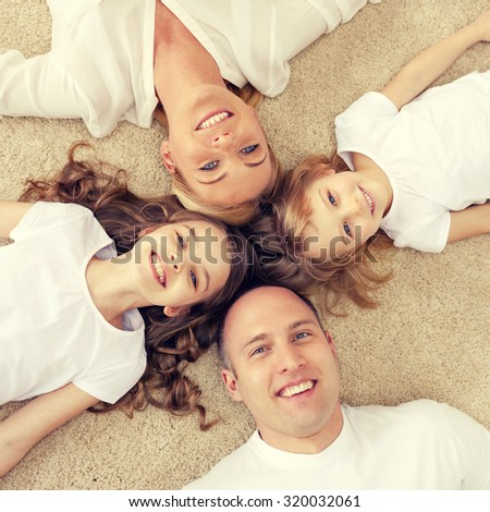 family, children and home concept - smiling family with and two little girls lying in circle on floor at home - stock photo