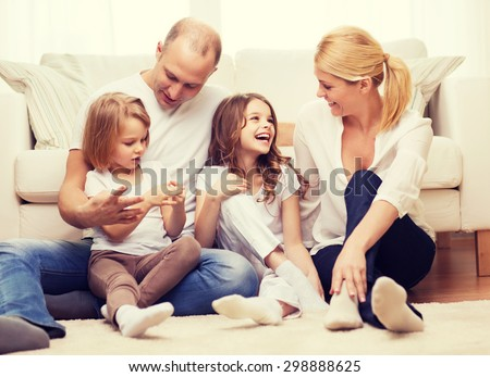 family, children and home concept - smiling family with and two little girls sitting on floor at home - stock photo