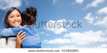 family, children and people concept - happy hugging mother and daughter over blue sky and clouds background - stock photo