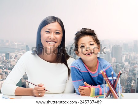 family, children and people concept - happy mother and daughter drawing over city background - stock photo
