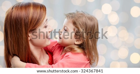 family, children and people concept - happy mother and little daughter hugging over holidays lights background - stock photo