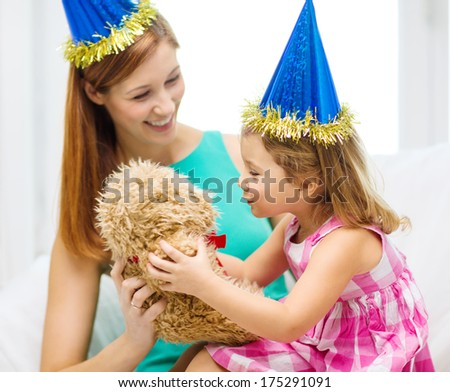 family, children, celebration and happy people concept - happy mother and daughter in blue party hats with teddy bear