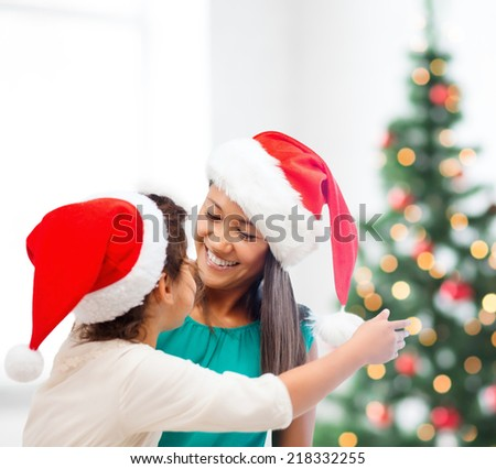family, children, christmas, x-mas and happy people concept - hugging mother and daughter in santa helper hats - stock photo