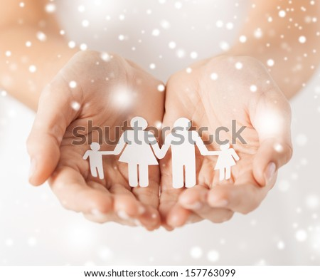 family, children, christmas, x-mas and happy people concept - woman cupped hands showing paper man family - stock photo