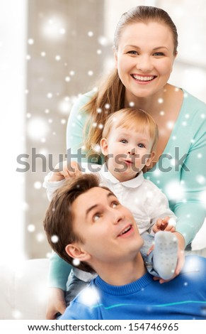 family, children, christmas, x-mas, love concept - happy parents playing with adorable baby - stock photo