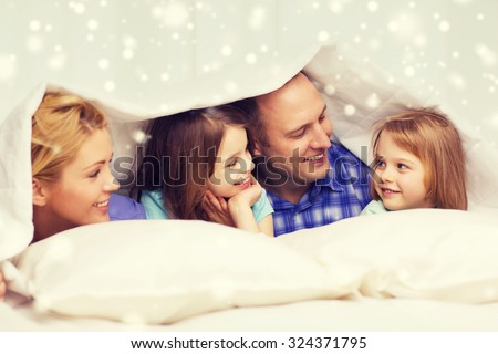 family, children, comfort, bedding and home concept - happy family with two kids under blanket over snowflakes background - stock photo