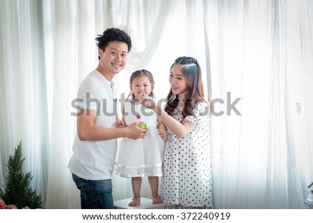 family, children, education, school and happy people concept - happy father mother and daughter Play feeding daughter.Backlit shot