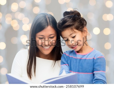 family, children, education, school and happy people concept - happy mother and daughter reading book over holidays lights background - stock photo