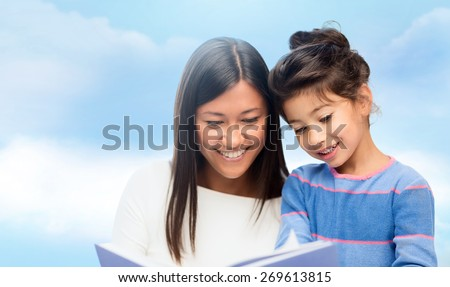 family, children, education, school and happy people concept - happy mother and daughter reading book over blue sky background - stock photo