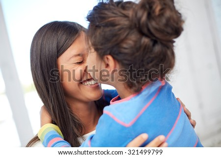 family, children, love and happy people concept - happy little girl hugging mother and kissing her on nose at home - stock photo