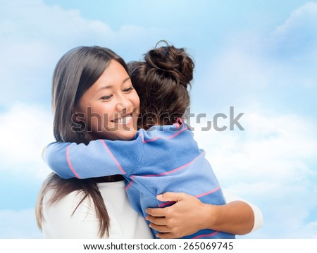 family, children, love and happy people concept - happy mother and daughter hugging over blue sky background - stock photo