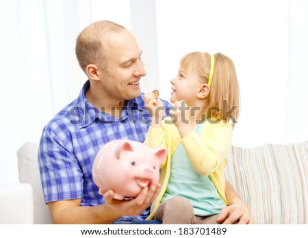 family, children, money, investmen and happy people concept - happy father and daughter with big pink piggy bank - stock photo
