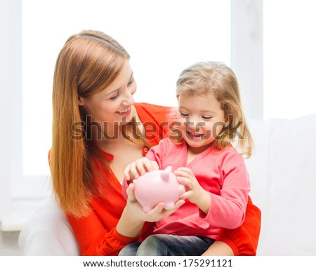 family, children, money, investmen and happy people concept - happy mother and daughter with small pink piggy bank - stock photo