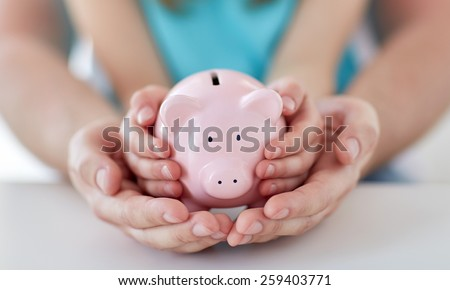 family, children, money, investments and people concept - close up of father and daughter hands holding pink piggy bank - stock photo