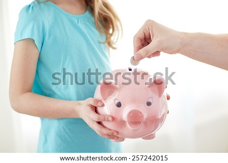 family, children, money, investments and people concept - close up of girl holding piggy bank and male hand putting coin into it