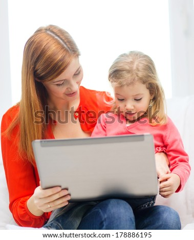 family, children, parenthood, technology and internet concept - happy mother and daughter with laptop computer at home - stock photo