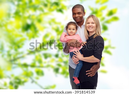 family, children, race and nationality concept - happy multiracial mother, father and little child over green natural background - stock photo