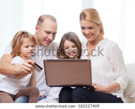 family, children, technology, money and home concept - smiling family and two little girls with laptop and credit card at home