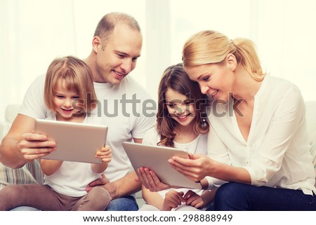 family, children, technology, money and home concept - smiling family and two little girls with tablet pc computers at home