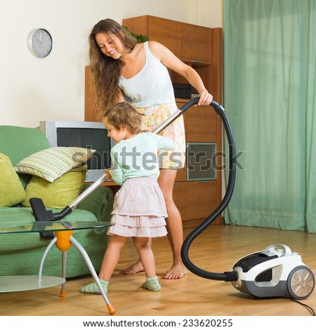 Family chores with vacuum cleaner in living room at home  - stock photo