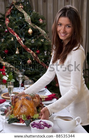 Family christmas dinner celebration. Woman holding Roasted turkey, red candles, fir tree ornament decoration, rich table with meals, champagne glasses, pie, grapes and vegetables - stock photo