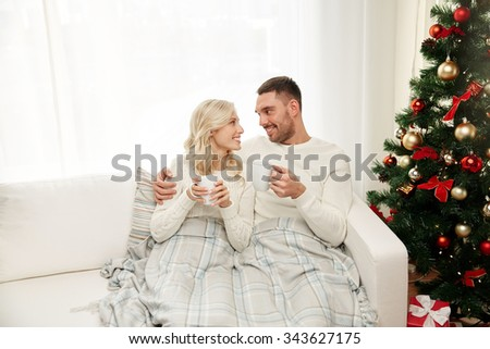 family, christmas, holidays, love and people concept - happy couple covered with plaid drinking tea and sitting on sofa at home