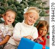 Family Christmas - three children having received gifts showing them around - stock photo