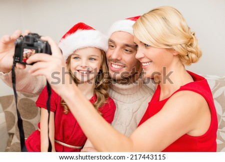 family, christmas, x-mas, happiness and people concept - smiling family in santa helper hats taking picture with photo camera - stock photo