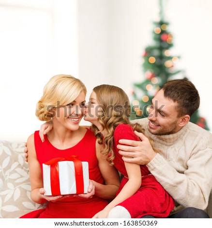 family, christmas, x-mas, winter, happiness and people concept - adorable child kisses her mother and gives present - stock photo