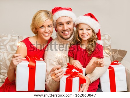 family, christmas, x-mas, winter, happiness and people concept - smiling family in santa helper hats with many gift boxes and bengal lights - stock photo